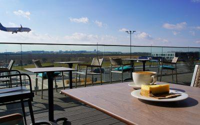 Kavárna svýhledem na letiště apřistávající letadla, to je Premium Outlet Prague